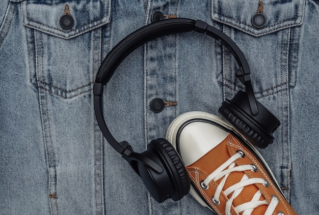 Juventude, roupas e acessórios hipster. tênis com fones de ouvido no fundo da jaqueta jeans. vista do topo. postura plana