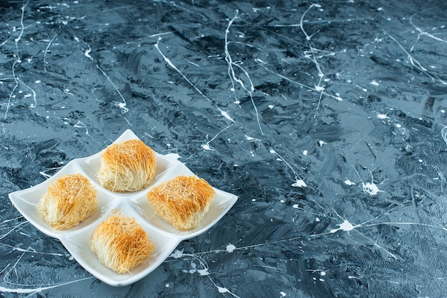 Kadayif de sobremesa turca em um prato, na mesa azul.