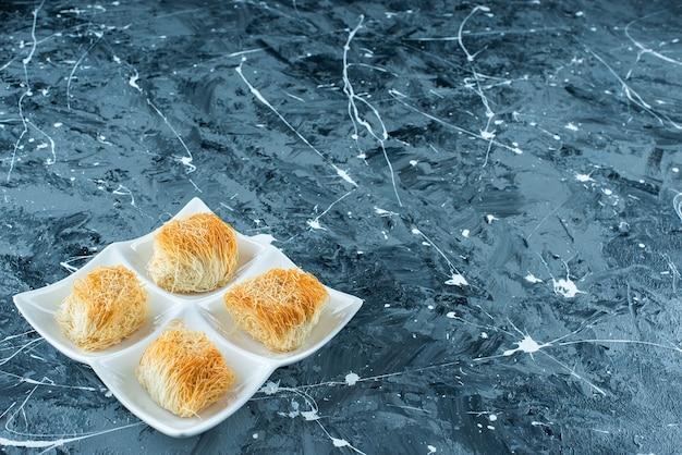 Kadayif de sobremesa turca em um prato, sobre o fundo azul.