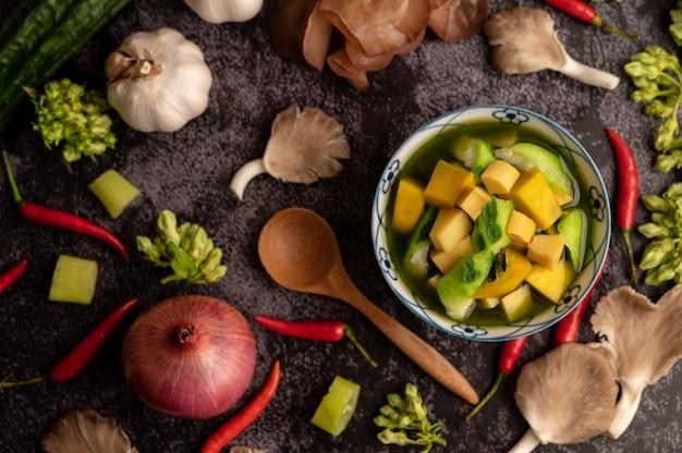 Kaeng liang em uma tigela com especiarias sobre um piso de cimento preto.