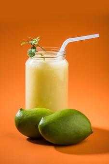 Kairi panha ou panna ou raw mango drink é uma bebida tradicional e popular no verão indiano servida em um copo sobre um fundo colorido ou de madeira. foco seletivo