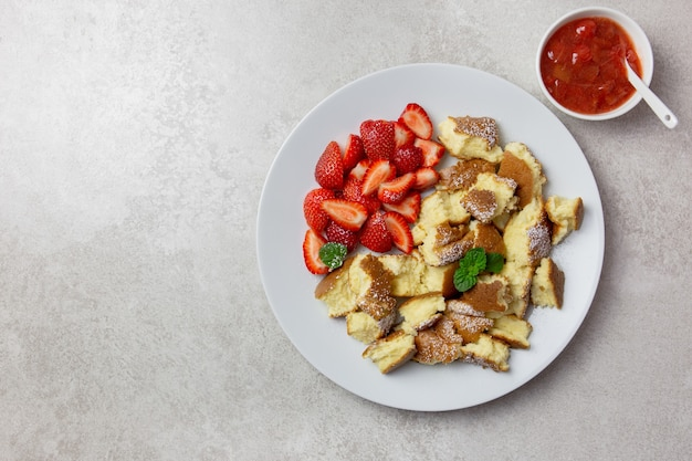 Kaiserschmarren ou kaiserschmarrn, sobremesa tradicional austríaca ou alemã de panqueca doce com frutas frescas, geleia de morango ou rote grutze e molho de pudim de baunilha