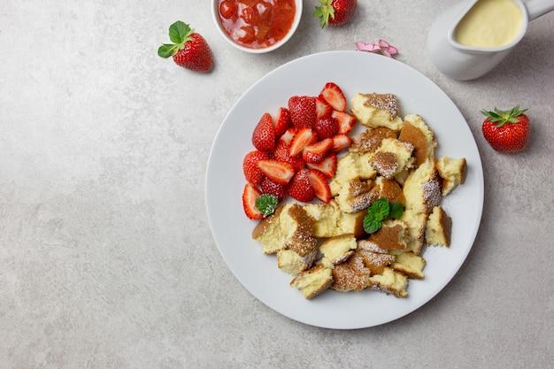 Kaiserschmarrn, sobremesa tradicional austríaca ou alemã de panqueca doce, com baga, geleia de morango ou rote grutze e molho de pudim de baunilha.