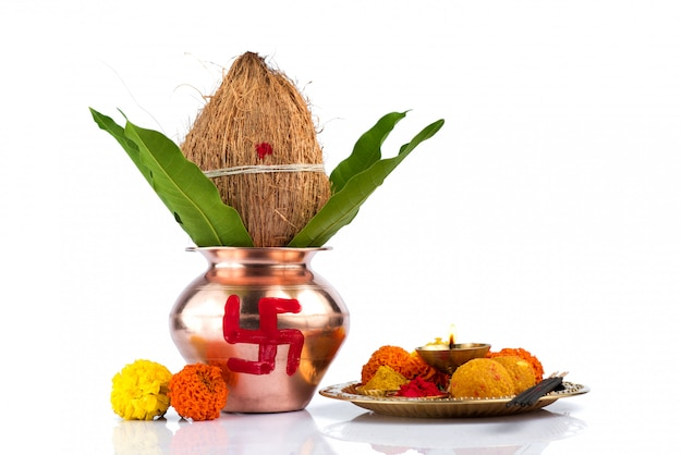 Kalash de cobre com folhas de coco e manga e thali pooja com diya, kumkum e doces com decoração floral. essencial no puja hindu.