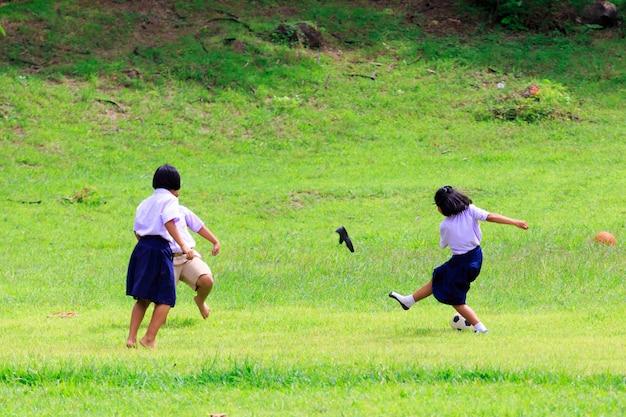 Kanchanaburi, tailândia - 25 de agosto de 2017: estudante tailandês que joga o futebol no campo verde na escola.