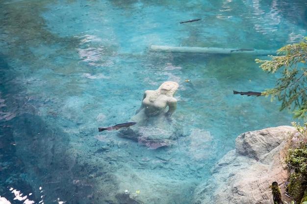Kandersteg suíça - vista de blausee com a estátua de uma mulher no lago, raphael fuchs