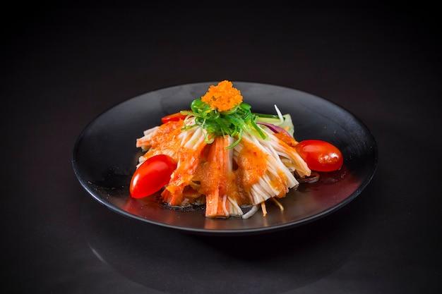 Kani salada coberto wakame, comida japonesa em fundo preto, comida saudável