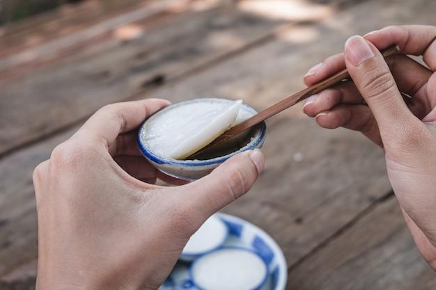 Kanom thuay, creme de leite de coco tailandês cozido no vapor na mesa de madeira