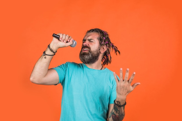 Karaokê. homem cantando com microfone. registros de estúdio. homem barbudo canta no microfone. microfone. cante uma canção. cantando em estúdio.