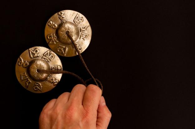 Karatalas de ouro pratos tingsha tibetano para meditação encontra-se na mão do homem