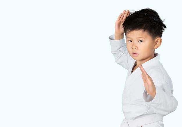 Karate boy asiático em quimono branco no fundo