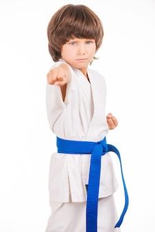Karate kid. garotinho fazendo movimentos de artes marciais enquanto está isolado no fundo branco