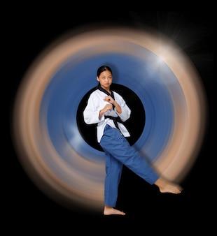 Karate taekwondo a menina adolescente gira em torno de sua perna flexível e gira como um néon. atleta jovem asiática mulher usa uniforme esporte tradicional sobre fundo preto comprimento total isolado