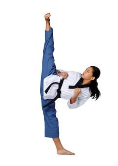 Karate taekwondo menina adolescente pratica chute de luta e perna alta no nível da faixa preta. atleta jovem asiática mulher usa uniforme esporte tradicional sobre fundo branco comprimento total isolado