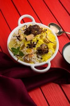 Kashmiri mutton gosht ou lamb biryani preparado em arroz basmati servido com molho de iogurte sobre fundo temperamental, foco seletivo