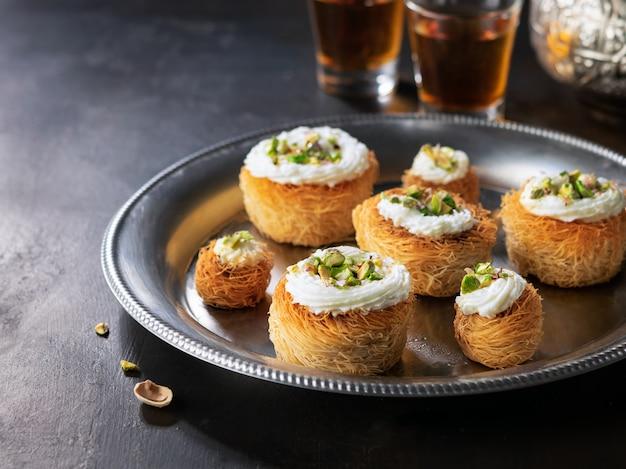 Kataifi, kadayif, kunafa, bolinhos do ninho da pastelaria do baklava com pistachios com chá.