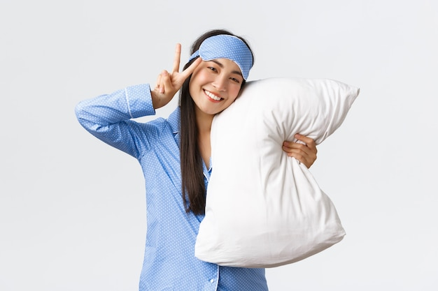 Kawaii feliz sorridente menina asiática na máscara de dormir azul e pijama, abraçando o travesseiro e mostrando o sinal da paz, sentindo-se bem depois de uma boa noite de sono, deitada na cama durante a festa do pijama, fundo branco.
