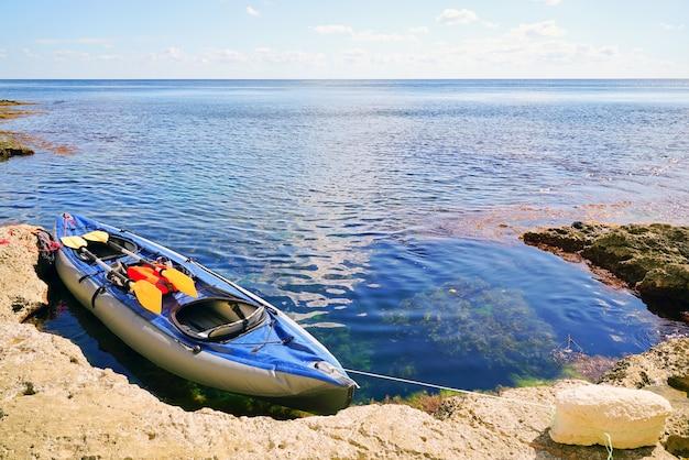 Kayak com remos na pitoresca praia de pedra.