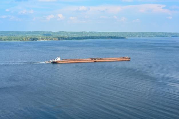 Kazan, rússia, 30 de agosto de 2021 um rebocador articulado e um navio graneleiro transporta areia e const