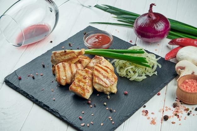 Kebab apetitoso da galinha com especiarias e cebolas em uma bandeja preta da ardósia em um fundo branco. shahlik. feche acima da porção de carne grelhada