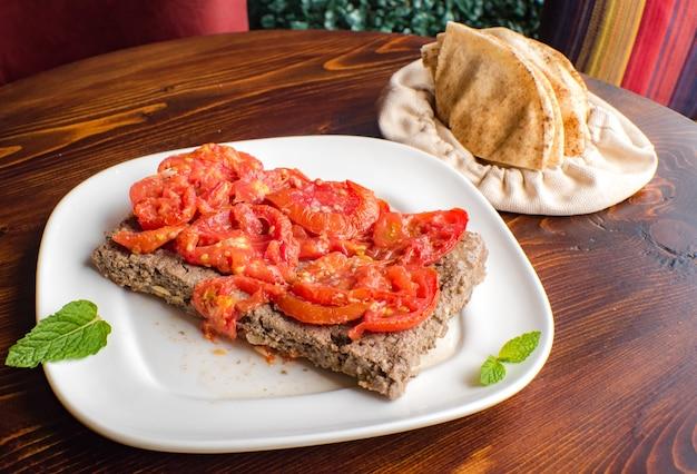 Kebab árabe picante com tomate por cima em turco no fundo de madeira