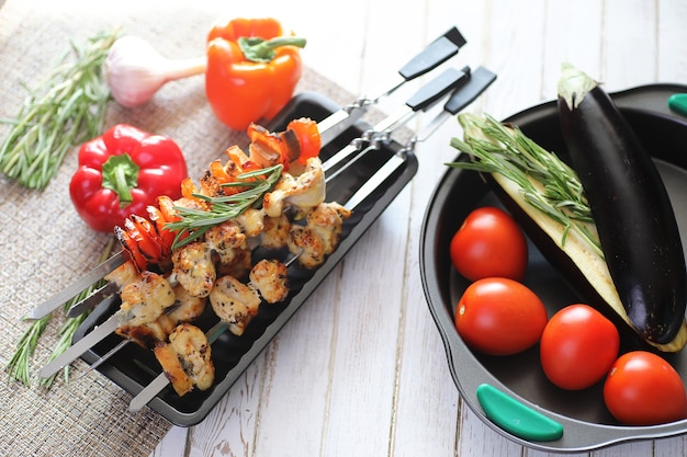 Kebab cozido em espetos de metal com legumes servidos na mesa branca