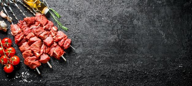 Kebab cru com tomate em um galho, óleo e alho