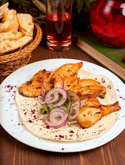 Kebab de asas de frango grelhado servido com composto, salada de legumes de cebola e ervas em chapa branca