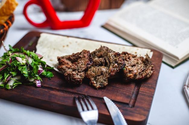 Kebab de basturma de vista lateral no pão pita com cebola e ervas