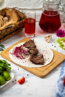 Kebab de carne com cebola, sumakh e lavash em uma placa de madeira servida com vinho e legumes