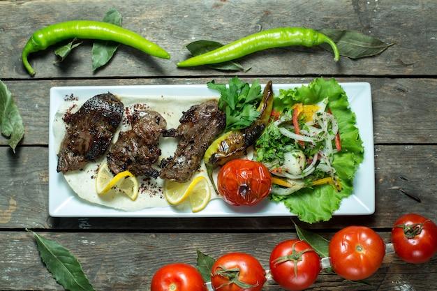 Kebab de carne de bovino, servido com cebola e tomate grelhado na bandeja