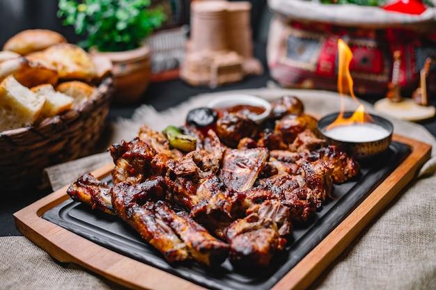 Kebab de carne de vista lateral com batatas grelhadas e legumes com molho e fogo em uma placa
