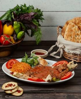 Kebab de carne decorado com fatia de tomate, servido com bulgur, pão e legumes