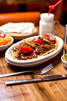 Kebab de carne turco, guarnecido com legumes grelhados ao molho de tomate picante