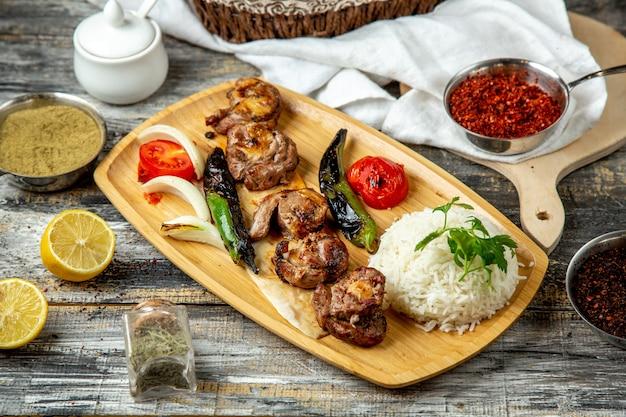 Kebab de cordeiro arroz pimenta cebola tomate vista lateral