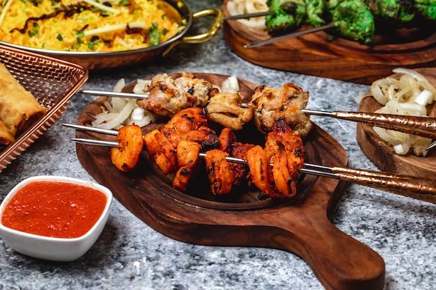 Kebab de cordeiro de vista lateral com cebola e molho em uma placa de camarão grelhado
