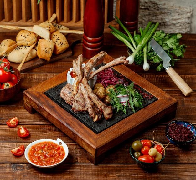 Kebab de costela de cordeiro servido com ervas frescas, batata bebê e molho de tomate
