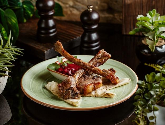 Kebab de costelas de cordeiro servido com molho e pão sírio