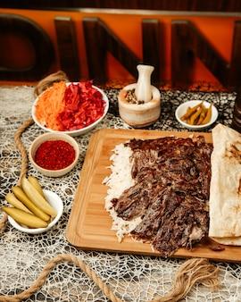 Kebab de doner de cordeiro colocado em cima de arroz coberto com pão sírio servido com picles e pimenta
