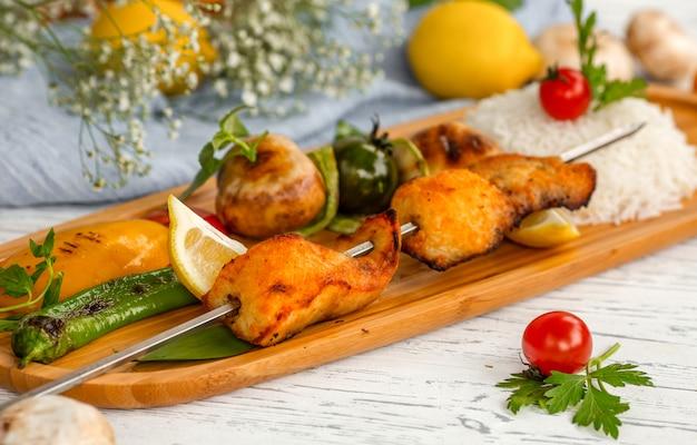 Kebab de esturjão e arroz com legumes fritos
