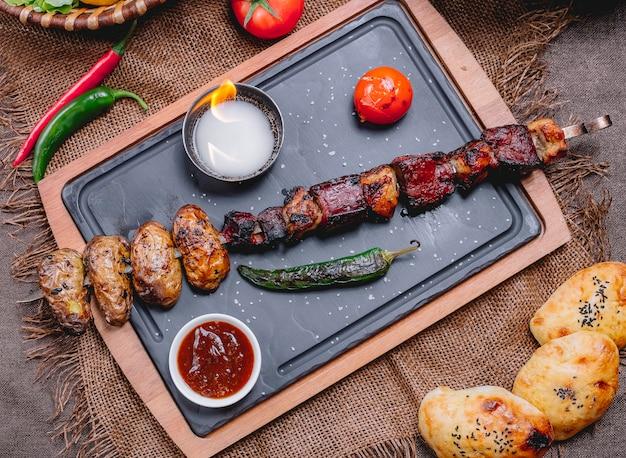 Kebab de fígado de vaca vista superior em um espeto com batatas e tomate com pimenta verde grelhada e molho em uma bandeja