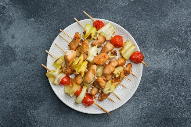 Kebab de frango, abobrinha e tomate no espeto em um prato.