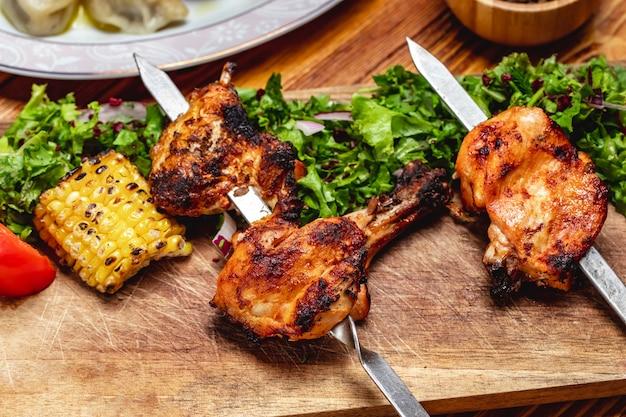 Kebab de frango de vista lateral com verdes alface tomate cebola vermelha milho grelhado e bérberis secas em cima da mesa