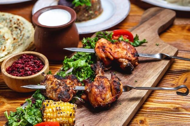 Kebab de frango de vista lateral com verdes tomate cebola vermelha bérberis secas e iogurte em cima da mesa