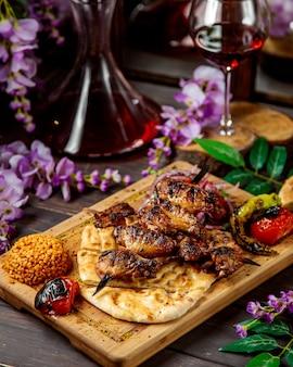Kebab de frango no espeto, servido com legumes e pão grelhados com bulgur
