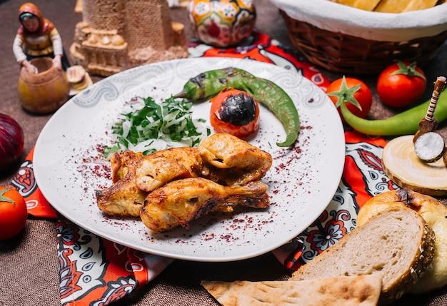 Kebab de frango vista frontal com tomate e pimenta na grelha com cebola e ervas