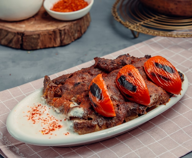 Kebab de iskender com tomates fritos