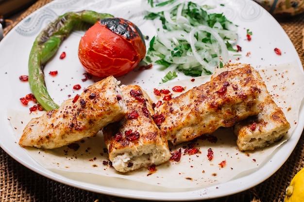 Kebab de lula de frango vista frontal no pão pita com tomate e pimenta grelhada com cebola e ervas