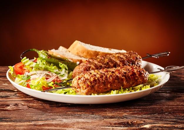 Kebab de lule caucasiano, churrasco de carne com salada verde e fatias de pão,