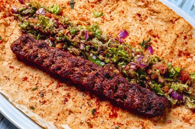 Kebab de lulya de vista lateral com cebola vermelha geens sal pimenta verde e pimenta no pão árabe